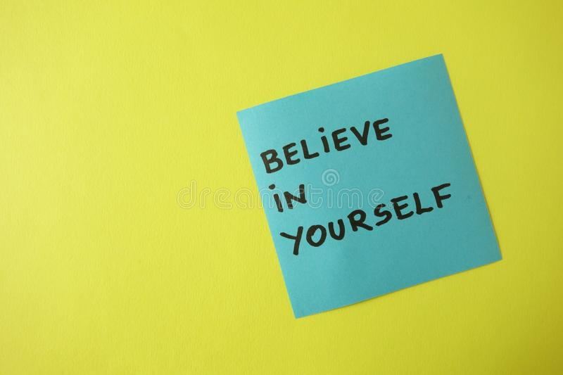 Believe in yourself written on blue sticky note, motivation concept. Believe in yourself written on blue sticky note on yellow background with copy space royalty free stock images