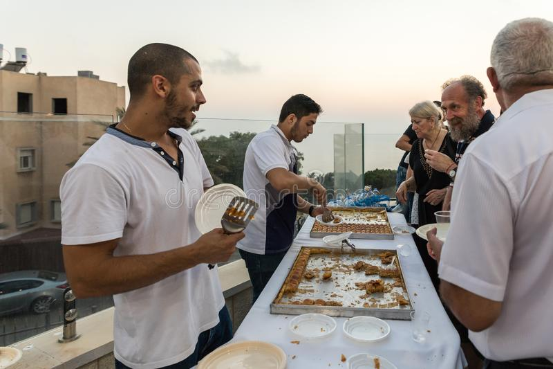 Believers treat visitors with sweets in the evening in the courtyard of the Ahmadiyya Shaykh Mahmud mosque in Haifa city in Israel. Haifa, Israel, July 11, 2019 stock images