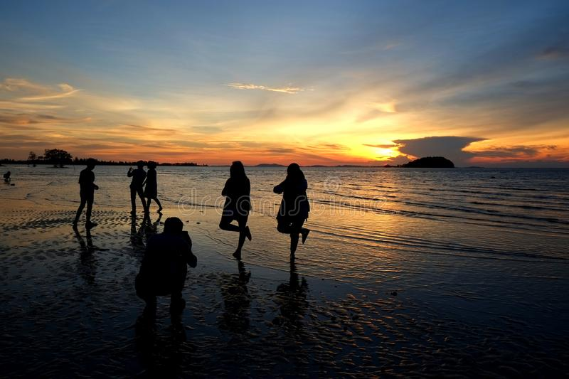 Belitung Sunset - Taking Photos at the Beach. A group of people having fun posing and taking photos at a beach during the low tide against a backdrop of a stock photo