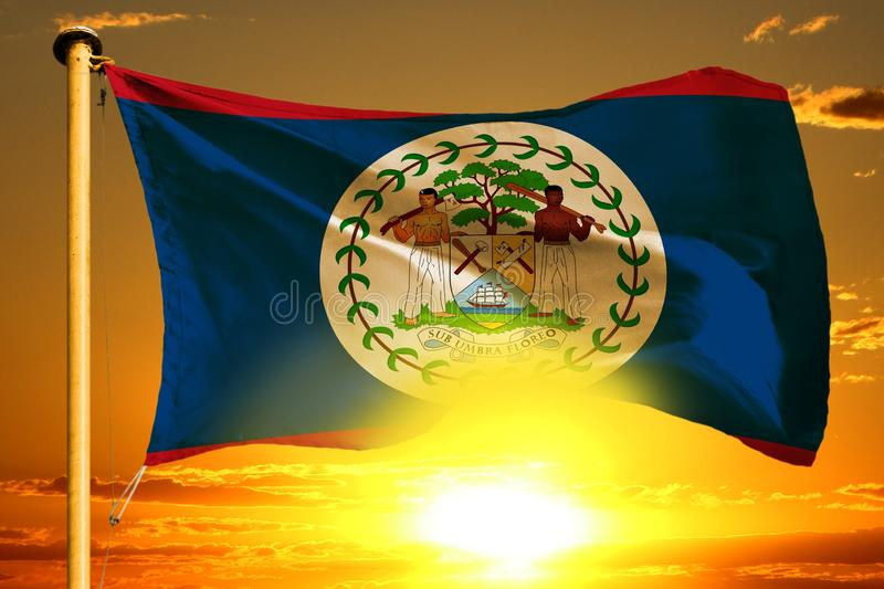 Belize flag weaving on the beautiful orange sunset with clouds background royalty free stock image