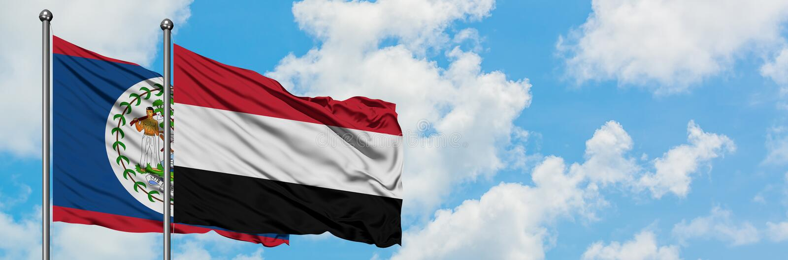 Belize and Yemen flag waving in the wind against white cloudy blue sky together. Diplomacy concept, international relations. Consul, diplomat, ambassador royalty free stock images