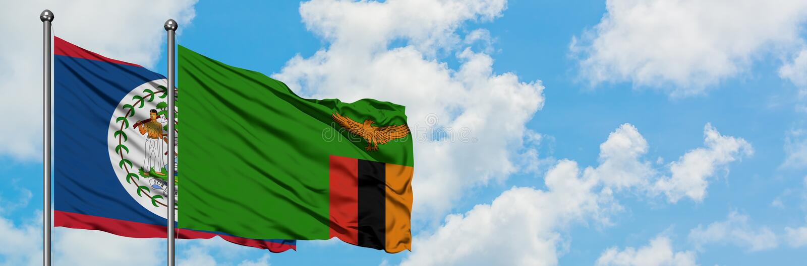 Belize and Zambia flag waving in the wind against white cloudy blue sky together. Diplomacy concept, international relations. Consul, diplomat, ambassador royalty free stock image