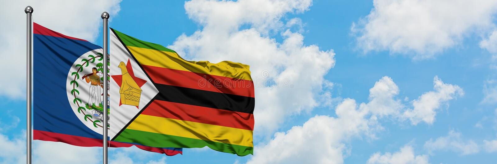 Belize and Zimbabwe flag waving in the wind against white cloudy blue sky together. Diplomacy concept, international relations. Consul, diplomat, ambassador royalty free stock photography