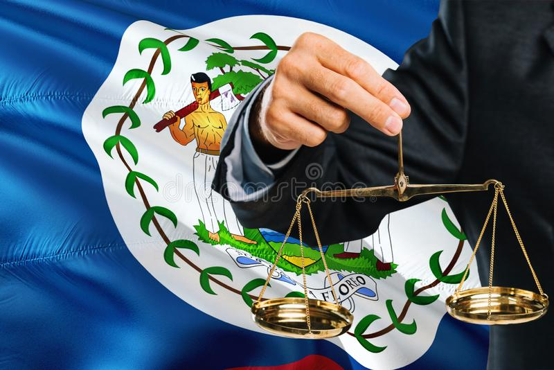 Belizean Judge is holding golden scales of justice with Belize waving flag background. Equality theme and legal concept stock image