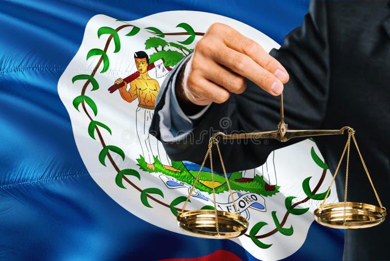Belizean sędzia trzyma złote skale sprawiedliwość z Belize falowania flagi tłem Równość temat i legalny pojęcie obraz stock