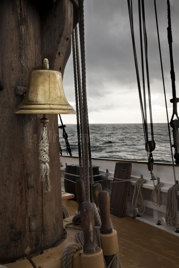 Bell in ancient ship deck. Stormy sea stock photography