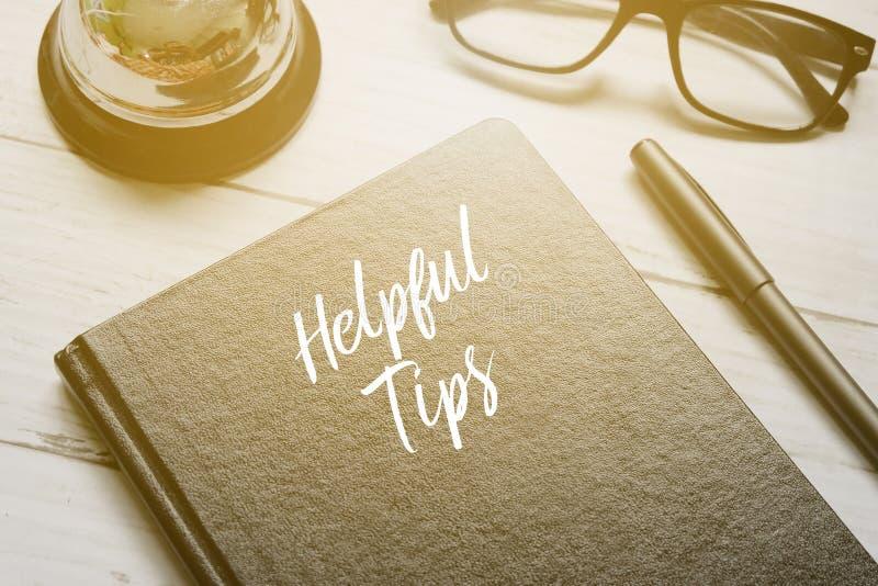 Bell, Brillen, Stift und Notizbuch, die mit HILFREICHEN TIPPS auf weißen hölzernen Hintergrund mit Sonne geschrieben werden, erwe stockbilder