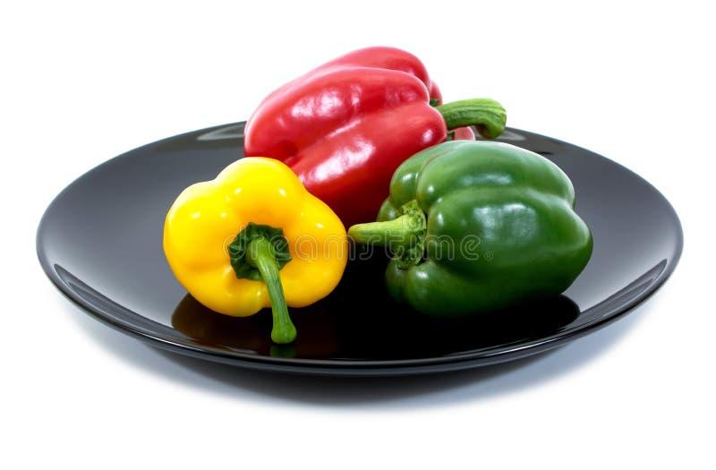 Bell-pepers in einer Platte über weißem Hintergrund Gemüsepaprikas im schwarzen Teller lokalisiert lizenzfreie stockfotografie
