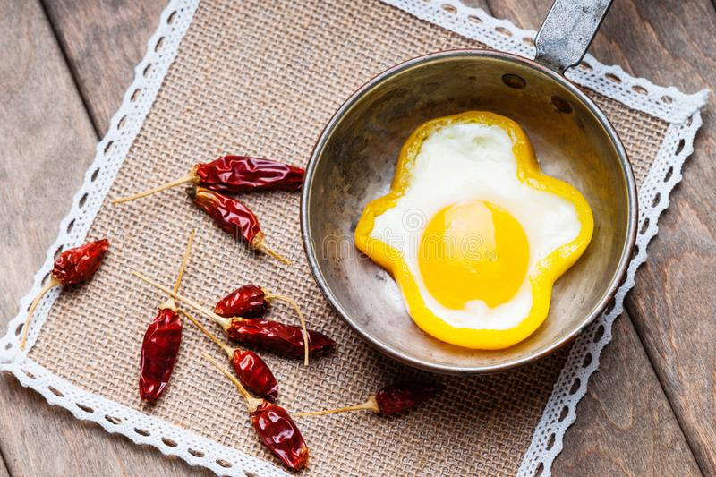 Bell pepper egg ring on a cooking pan and dried chili peppers stock photos