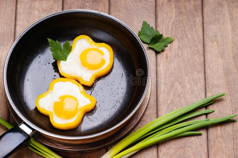 Bell pepper egg rings on a cooking pan, parsley and green onion. On the wooden table royalty free stock photo