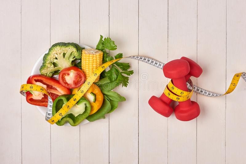 Bell pepper with measuring tape, dumbbells and bottle of water, royalty free stock images