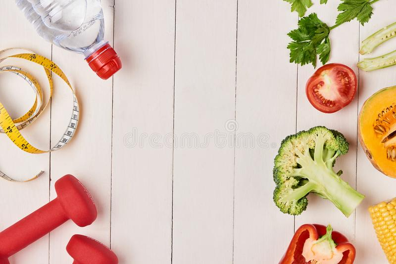 Bell pepper with measuring tape, dumbbells and bottle of water, stock photo
