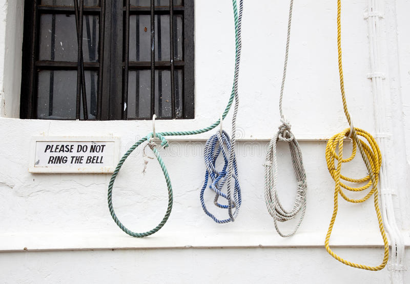 Bell ropes. A bell ropes, hanging on the wall of the church with a sign that tells people not ring the bell royalty free stock images