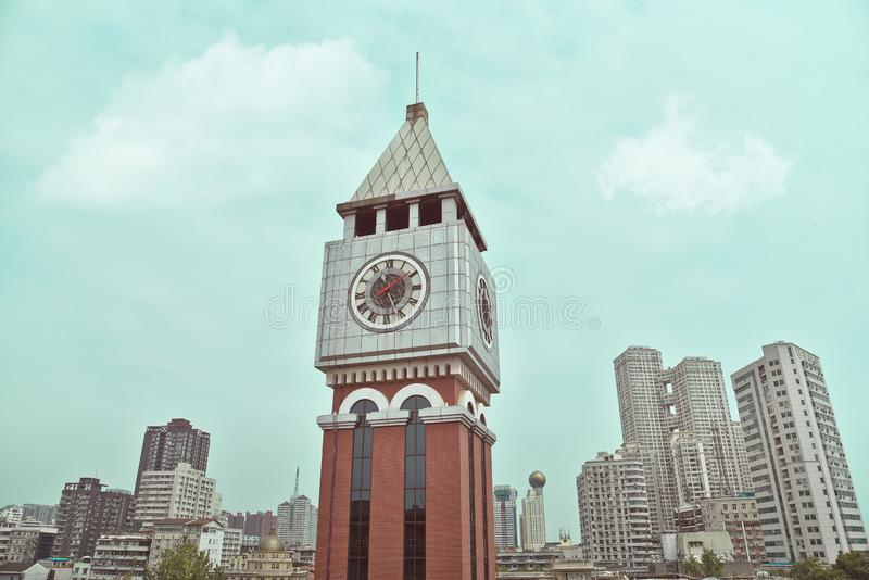 Bell tower with blue sky and modern buildings in wuhan city stock photography