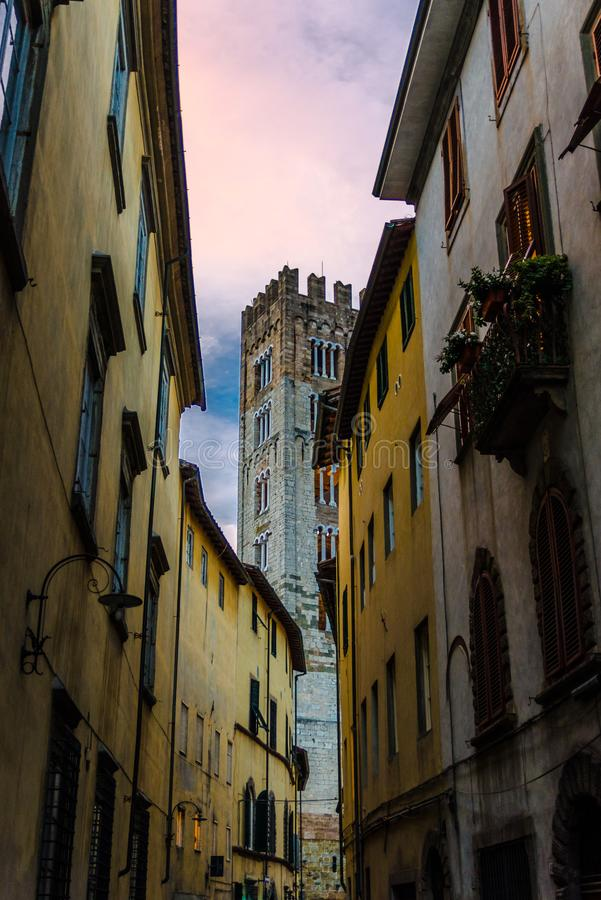 Bell tower of Chiesa di San Frediano catholic church view through narrow street in historical centre of old medieval town Lucca royalty free stock photo