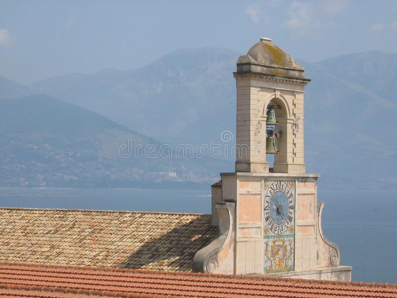 The bell tower of the church of the Holy Trinity of Gaeta with painted walls near the sea. Italy. stock photo