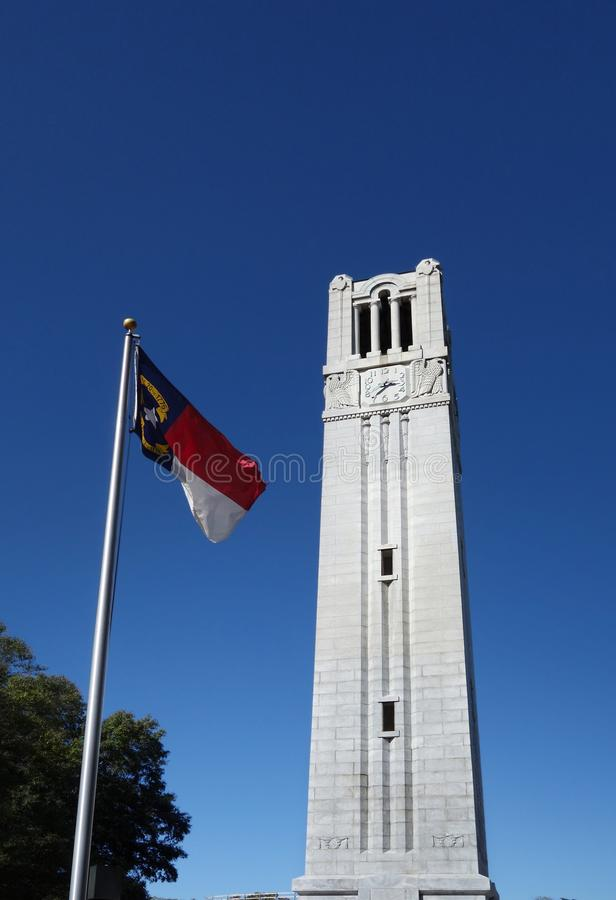 Bell tower and flag. The bell tower and North Carolina state flag on the campus of NC State University stock image