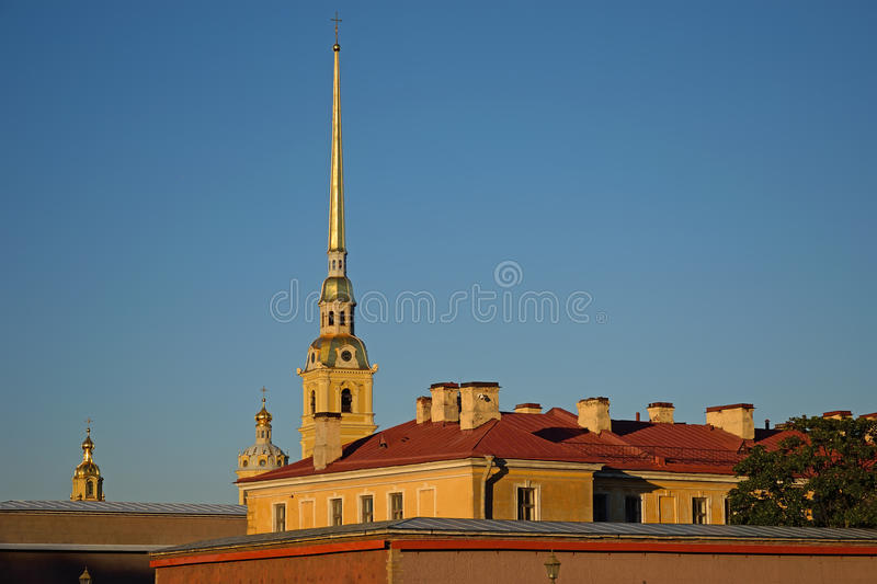 The bell tower of Peter and Paul Cathedral fortress on Hare island in St. Petersburg over the rooftops stock images