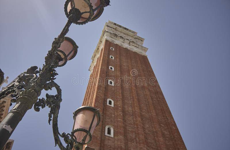 The bell tower of St. Mark`s Square in Venice. Taken from the bottom with the street lamps used for public lighting stock photography