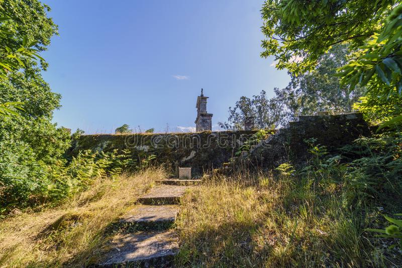 Bell tower and stone cross on the top of the hill called. `La Espenuca` in Galicia Spain.Clear sky with some clouds. Without people royalty free stock images
