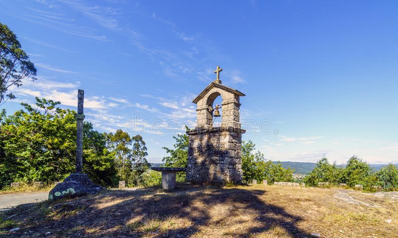 Bell tower and stone cross on the top of the hill called. `La Espenuca` in Galicia Spain.Clear sky with some clouds. Without people royalty free stock photo