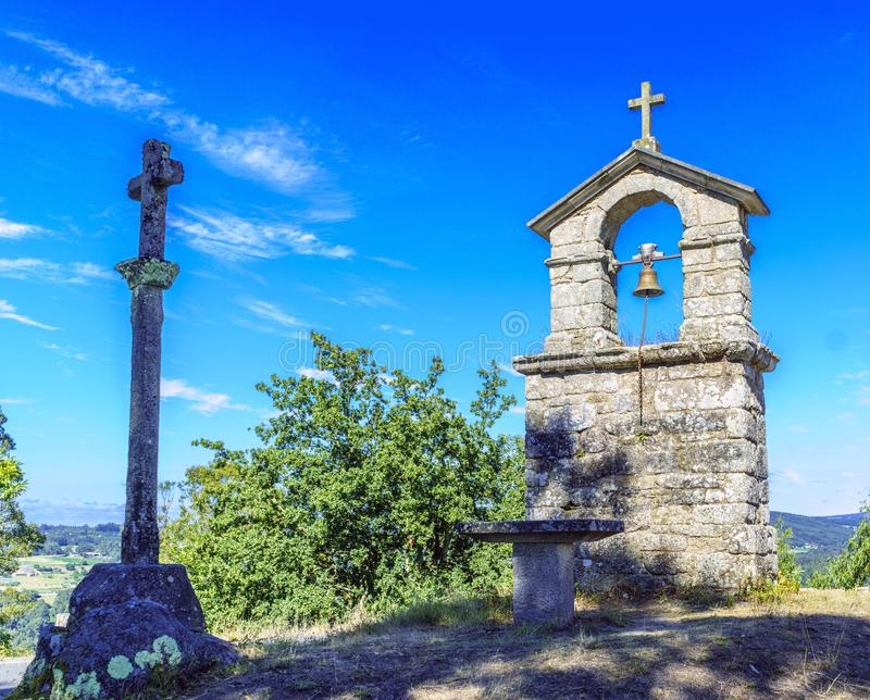 Bell tower and stone cross on the top of the hill called royalty free stock photography
