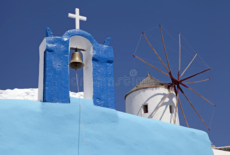 Bell tower and windmill in Oia village, Santorini, Greece royalty free stock images