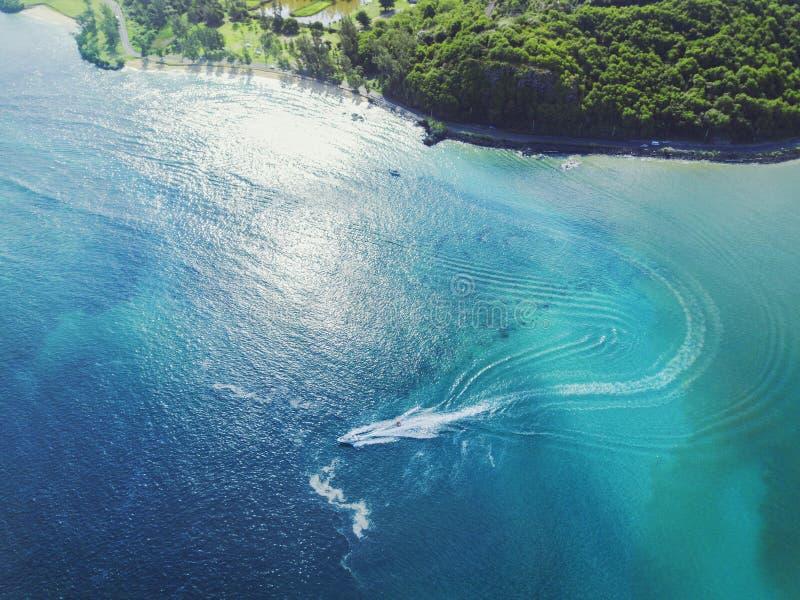 Bella acqua blu di zona costiera con la barca che passa velocemente immagine stock libera da diritti
