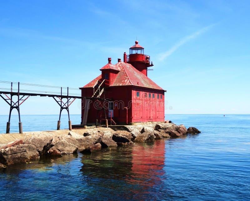 Bella acqua blu luminosa di sturgion della baia del faro storico di Wisconsin ed acqua pacifica calma del cielo con la riflession immagine stock