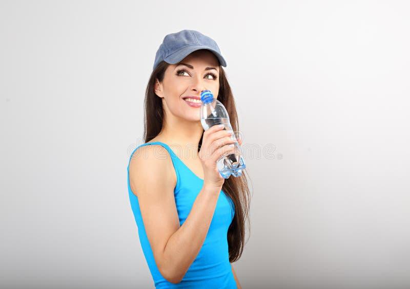 Bella acqua potabile di pensiero sportiva felice della donna dalla bottiglia dopo la formazione e cercatoe sul fondo blu dello st fotografie stock
