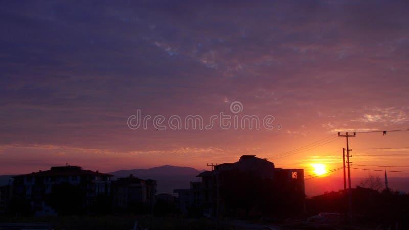 Bella alba che aumenta dalla montagna, costruzioni scure intorno fotografia stock