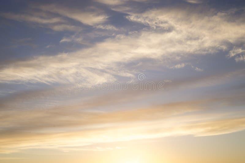 Bella alba delle tonalità dell'oro e del blu nelle nuvole immagini stock libere da diritti