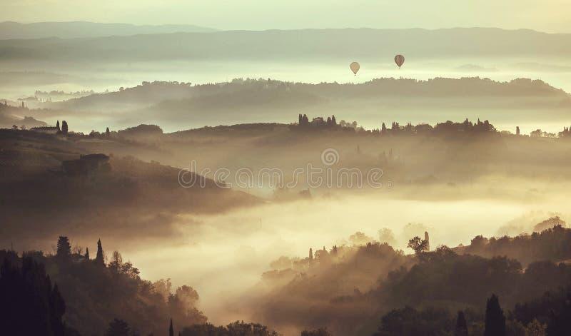 Bella alba sopra le colline in Toscana con gli alberi del giardino, palazzi, colline verdi Nebbia in campagna italiana fotografia stock libera da diritti