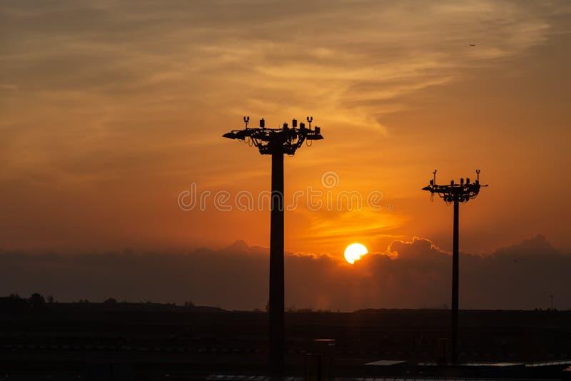Bella alba sotto le nuvole Torre della lampada dei riflettori sulle colonne all'aeroporto fotografie stock libere da diritti