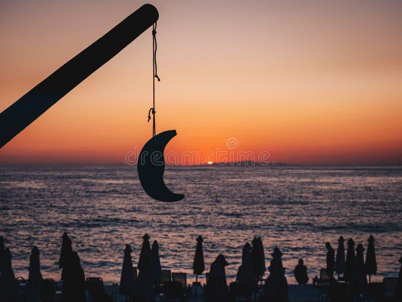 Bella alba in Thasos, Grecia con il sole che aumenta dal mare, turisti sulla spiaggia che guardano l'alba e una luna di modello immagine stock libera da diritti