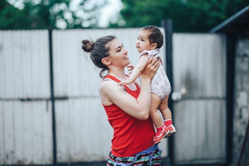 Bella aria aperta del bambino e della madre sull'iarda della casa Mummia di bellezza ed il suo gioco di un anno del bambino del b fotografia stock libera da diritti