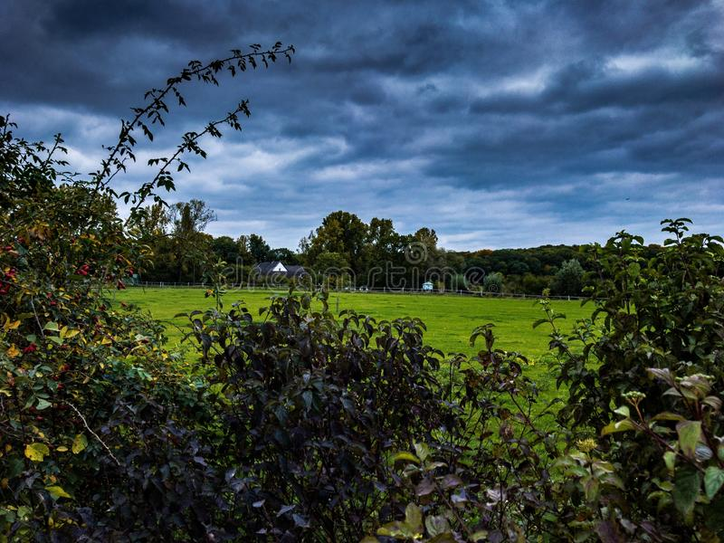 Bella azienda agricola tedesca in natura con cielo scuro nuvoloso fotografie stock libere da diritti