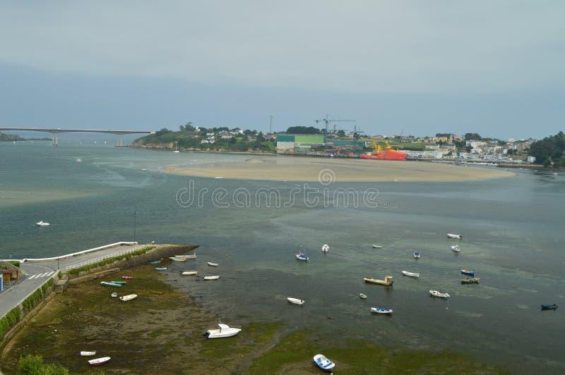Bella baia piena dei pescherecci con il porto industriale al fondo a Castropol immagini stock