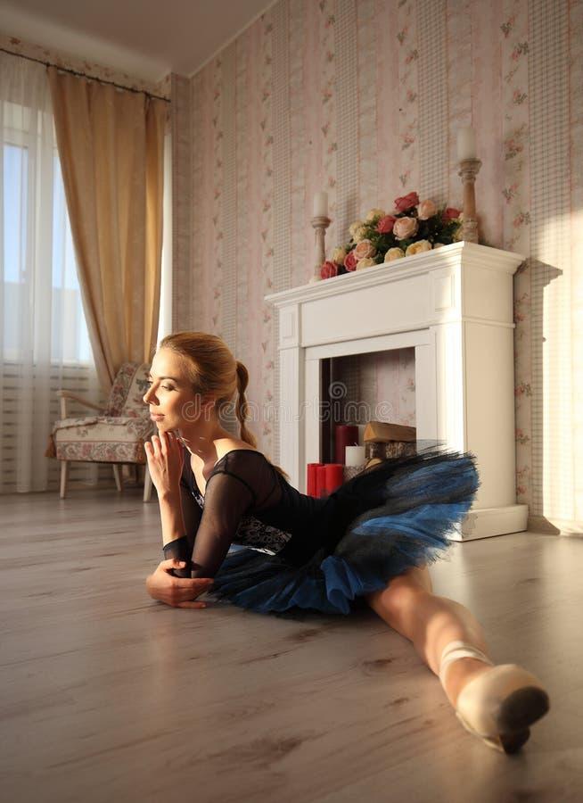 Bella ballerina della giovane donna che allunga scaldarsi nell'interno domestico, spaccatura sul pavimento, vista laterale immagine stock