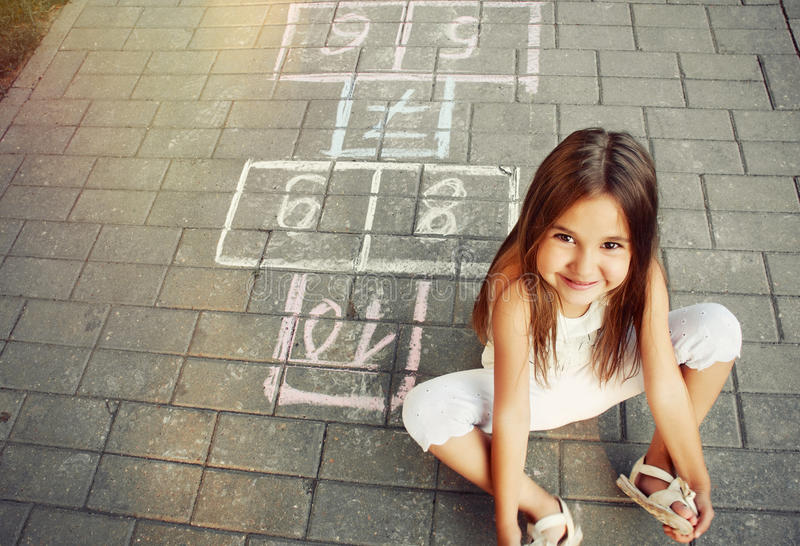 Bella bambina allegra che gioca a campana sul campo da giuoco immagine stock