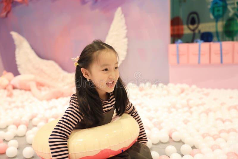 Bella bambina allegra che gioca la terra di piacere sul campo da giuoco immagine stock