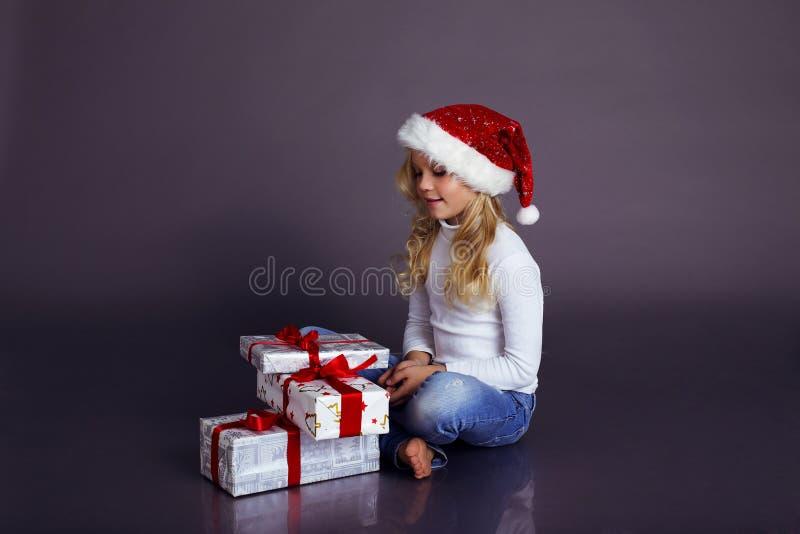Bella bambina in cappello e jeans di Santa che sorride e che tiene i presente fotografia stock