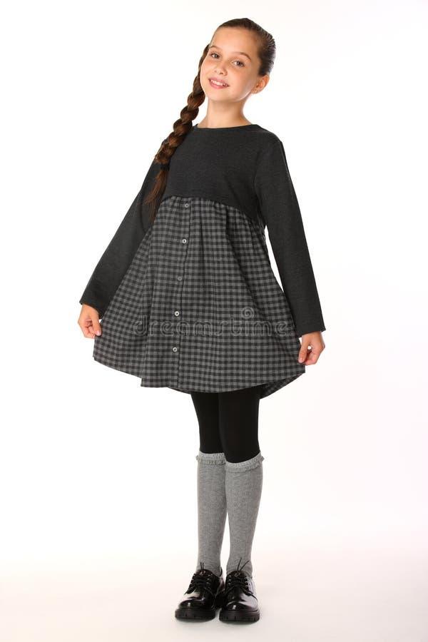 Bella bambina che posa in uniforme scolastico e felice fotografia stock