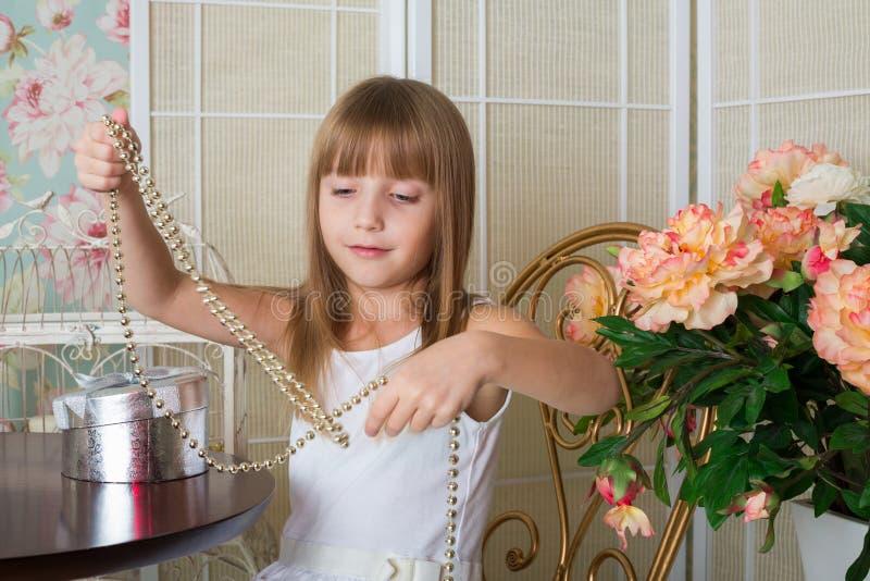 Bella bambina che si siede alla tavola immagine stock
