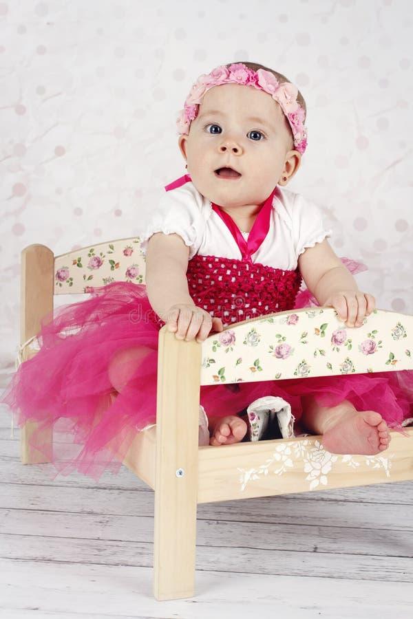 Bella bambina che si siede sul letto immagine stock libera da diritti