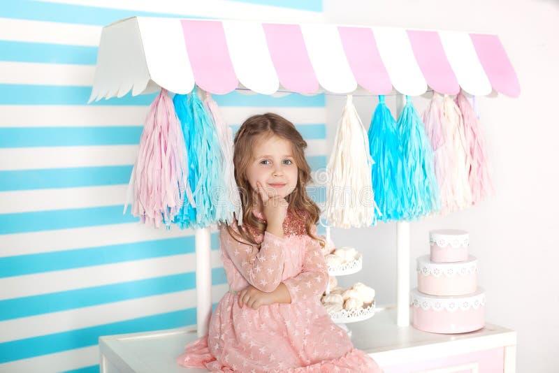 Bella bambina che si siede sulla tavola con le caramelle Barra del compleanno di Candy Ritratto di un primo piano del fronte del  fotografia stock