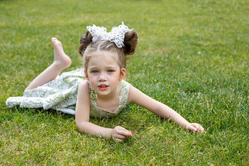 Bella bambina che si trova sull'erba immagine stock libera da diritti
