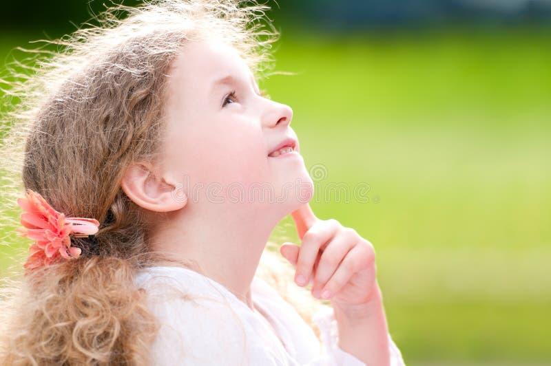 Bella bambina che sorride e che osserva in su immagini stock libere da diritti