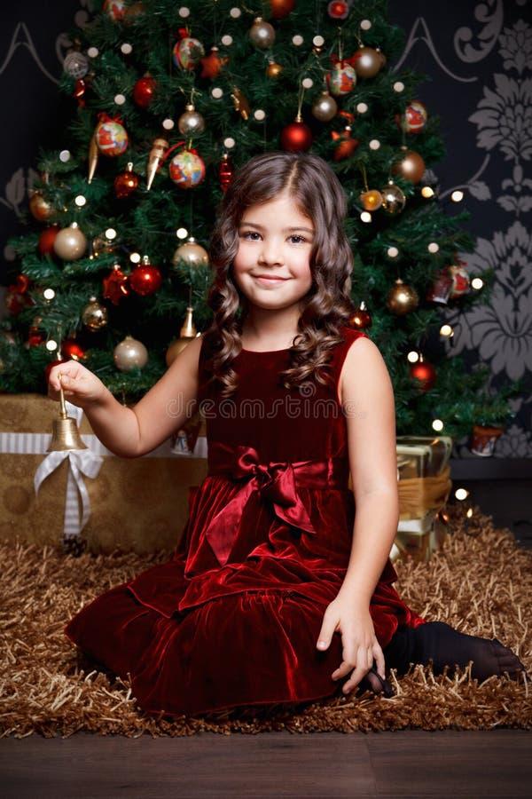 Bella bambina che suona una campana al Natale fotografia stock libera da diritti