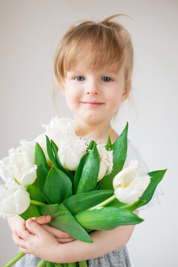 Bella bambina che tiene un mazzo dei fiori fotografia stock